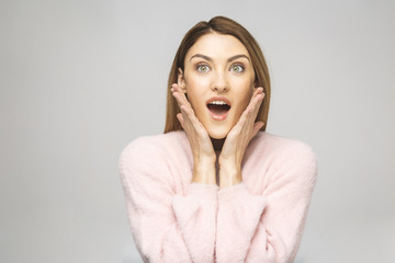Image of excited screaming young woman standing isolated over white background. Looking up.