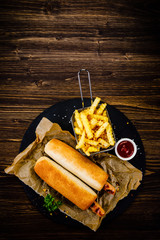 Hot dogs and french fries on black stone plate