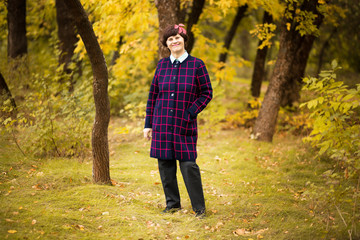 60 year old woman walk in gold autumn park