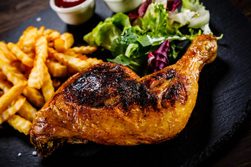 Grilled chicken leg with french fries and vegetables