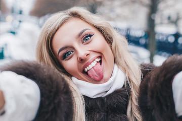 Beautiful girl takes funny winter selfie outdoor