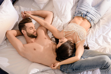 beautiful sexy couple lying in bed and holding hands in morning