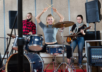 Rehearsal of music group with female drummer