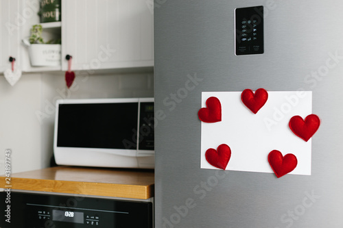 Handmade red felt heart shape magnets on refrigerator door