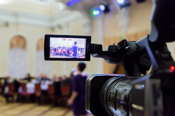 Video shooting at the event in the restaurant. Digital video camera with LCD display. People sit at tables in the background. Defocused background.