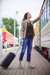 woman with luggage waves his hand near passenger railcar