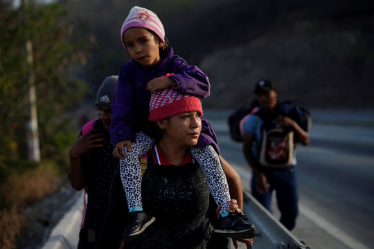 Tortilla maker from Honduras Edy Mavel carries her 5 years old daughter during their journey towards the United States, in Guastatoya, Guatemala