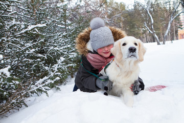 cute little girl with a dog, golden retriever, for a walk in winter