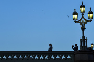 A man takes a picture of his friend on Westminster Bridge in London