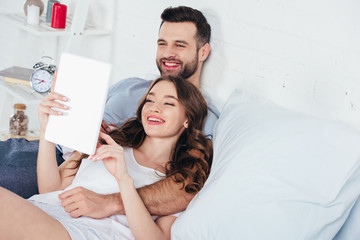 young couple relaxing, smiling and using digital tablet