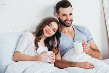 adult couple relaxing, lying on soft white bedding and holding cups
