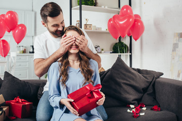 loving man covering woman eyes with hands in room with heart-shaped balloons