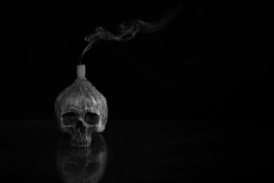 Skull which has extinguished candle on head and put on the mirror and blsck and white for background