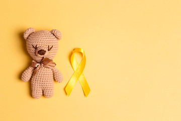 Children's toy with a Childhood Cancer Awareness Yellow Ribbon on yellow background.
