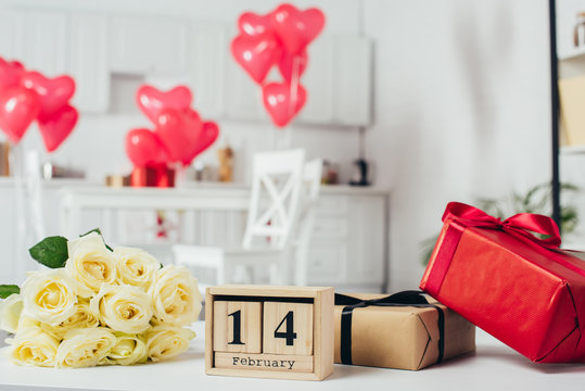 gift boxes with ribbons, roses bouquet and calendar with 14 February date on table with heart-shaped balloons on background