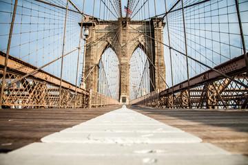 Empty Brooklyn Bridge promenade with bike lane and pedestrian lane during summer sunny day