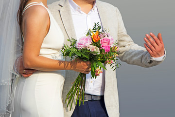Young newlywed just married posing in front of a gray background