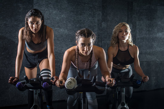 Group of three attractive sporty girls working out on exercise bicycles during cycling class indoors.