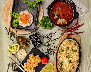 Top view flatlay japanese style business lunch including soup, salad, sushi and main meal at wooden table decorated background.