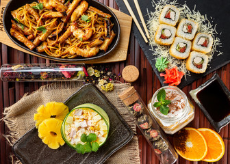 Top view flatlay japanese style business lunch including soup, salad, dessert and main meal at wooden table decorated background.