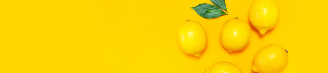 Wall Mural - Ripe juicy lemons and green leaves on bright yellow background. Lemon fruit, citrus minimal concept, vitamin C. Creative summer food minimalistic background. Flat lay, top view, copy space.