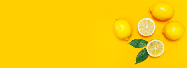 Ripe juicy lemons and green leaves on bright yellow background. Lemon fruit, citrus minimal...