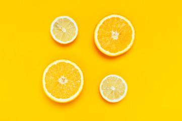 Wall Mural - Ripe juicy lemons, orange on bright yellow background. Lemon fruit, citrus minimal concept, vitamin C. Creative summer minimalistic background. Flat lay, top view, copy space.