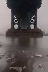 View on from under the Manhattan bridge on a foggy morning with long exposure