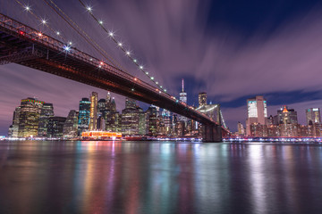 View on Financial district with Brooklyn bridge from east river at night with long exposure