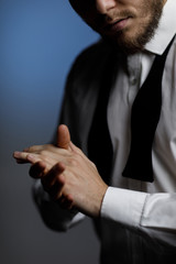 hands of young bearded man in shirt and untied bow tie