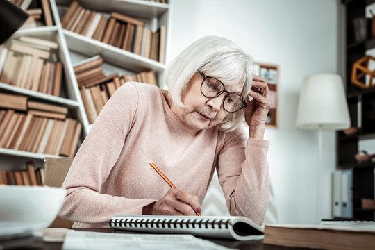 Concentrated senior female preparing task for lesson