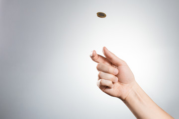 Hand throwing up a coin on gray background