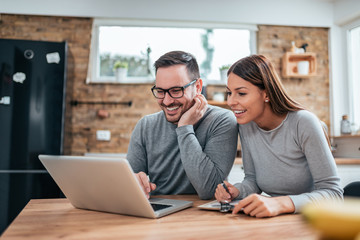 Smiling couple using laptop at the kitchen table. Wall mural