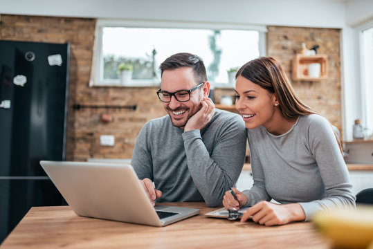 Smiling couple using laptop at the kitchen table.