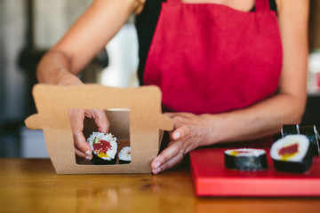 Crop woman serving sushi in carton box
