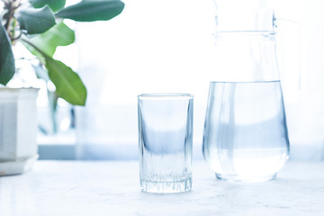 glass cup and carafe with water on a white table