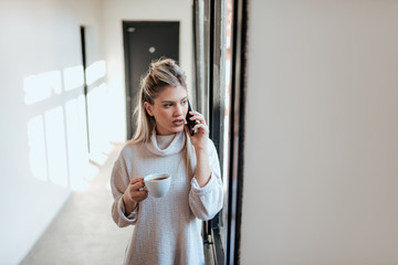 Confident casual businesswoman talking on the phone. Holding a cup of coffee and looking through window.