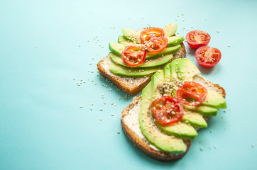 Flat lay of delicious toasts with sliced avocado, tomatoes and sesamum seeds on blue background with copyspace.