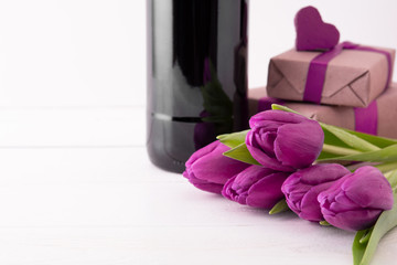 romantic gifts with flowers and wine on white background