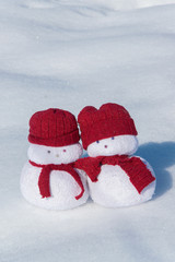 Two lovely snowmen toys on the white snow, holiday celebration concept