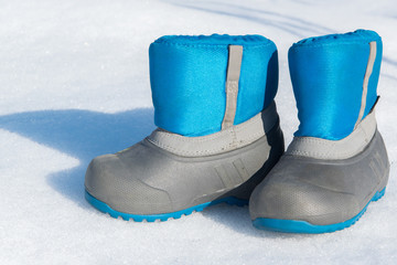 Pair of waterproof children boots on the snow, space for text