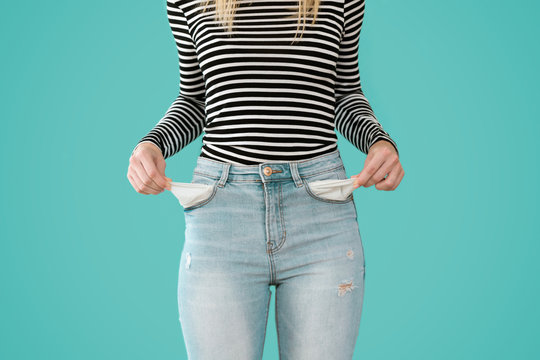 Young woman showing doesn't has nothing in her jeans pockets on blue background.