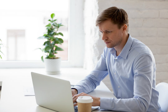 Focused businessman using laptop, looking at screen, typing, writing financial report, working on internet project, serious man, freelancer writing business email, online shopping at workplace