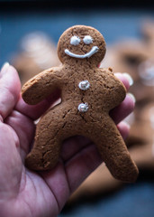 Hand holding a gingerbread man cookie