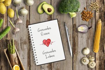 """gesunde Lebensmittel und Notizblock mit Aufschrift """"Gesundes Essen, Gesundes Leben"""" auf Holzuntergrund"""