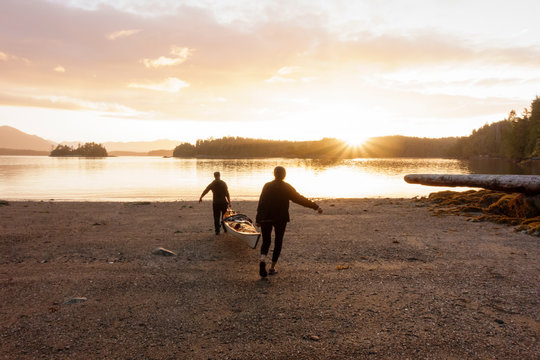 People couple carrying launching a sea kayak at sunrise in the remote wilderness, British Columbia, Canada. Adventure travel teamwork beginnings relationships concept.