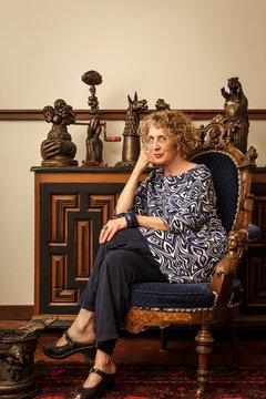 Portrait of female artist wearing eyeglasses sitting on chair in studio