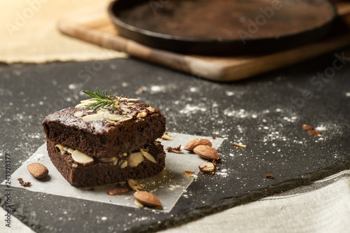 Homemade dark chocolate brownies topping with almond slices stacked