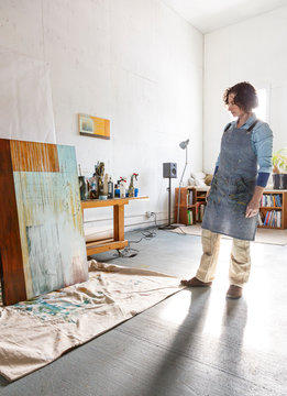 Creative woman artist working looking at a painting in her studio