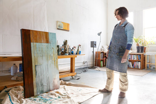 Female artist looking at painting in studio